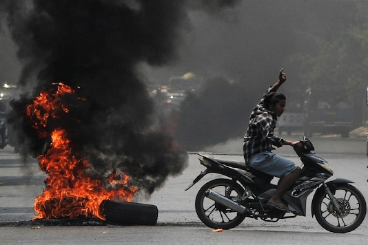 A man flashes the three-finger salute as he passes burning tires during a protest against the military coup, in Mandalay, Myanmar April 1, 2021. (Reuters)