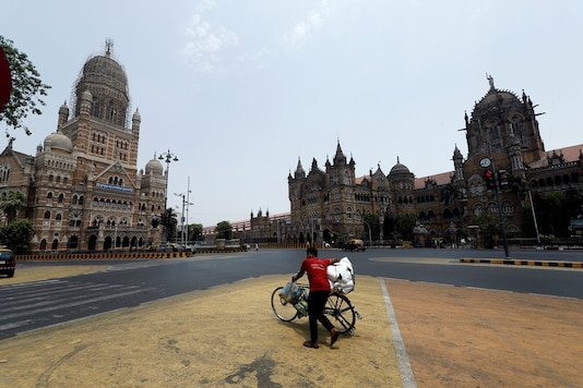 A man walks with his bicycle in front of the Brihanmumbai Municipal Corporation (BMC) building and the Chhatrapati Shivaji Maharaj Terminus (CSMT) during a weekend lockdown to limit the spread of the coronavirus disease (COVID-19) in Mumbai, India, April 10, 2021.