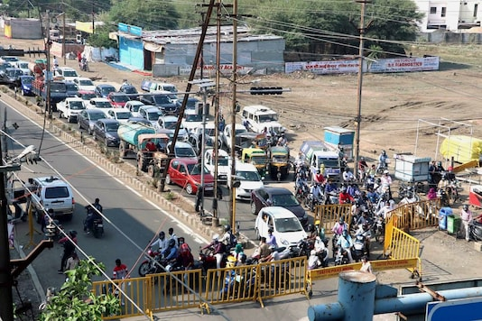 People with their vehicles out on a road during ongoing nine-day lockdown imposed due to rise in the COVID-19 cases, at Kolar locality in Bhopal, Monday. (PTI)