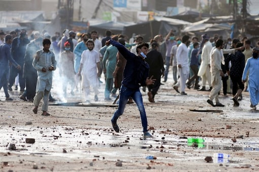 A supporter of the Tehreek-e-Labaik Pakistan Islamist political party hurls stones towards police during a protest against the arrest of their leader in Lahore, Pakistan. REUTERS/ File photo