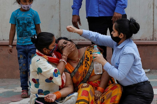 A woman is consoled after her husband died due to the coronavirus disease (COVID-19) outside a mortuary of a COVID-19 hospital in New Delhi. REUTERS