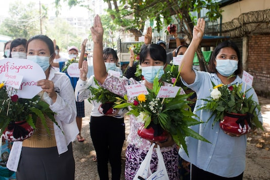 Women carry pots with flowers as they take part in a protest against the military coup in Yangon, Myanmar April 13, 2021. (Reuters)