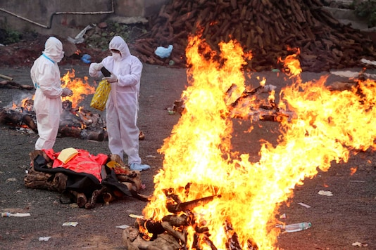 Family members wearing PPE kits, perform cremation of COVID-19 victims, in Bhopal, Thursday, April 15, 2021. (PTI Photo)