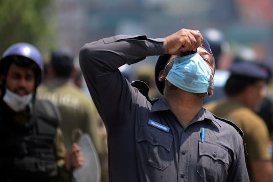 A police officer recovers from the blowback of tear gas during a protest by the supporters of the banned Islamist political party Tehrik-e-Labaik Pakistan (TLP) in Lahore, Pakistan April 18, 2021.REUTERS/Stringer