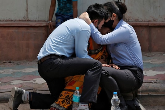 A woman is consoled by her children after her husband died due to the coronavirus disease (COVID-19) outside a mortuary of a COVID-19 hospital in New Delhi, India, April 15, 2021. REUTERS/Danish Siddiqui