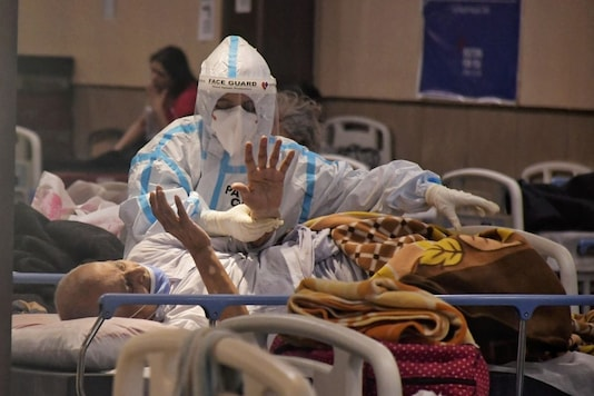New Delhi: A health worker inspects COVID-19 patients undergoing treatment at Shehnai Banquet Hall, converted into an isolation centre amid surge in coronavirus cases, near LNJP Hospital in New Delhi, Tuesday, April 20, 2021. (PTI Photo)(