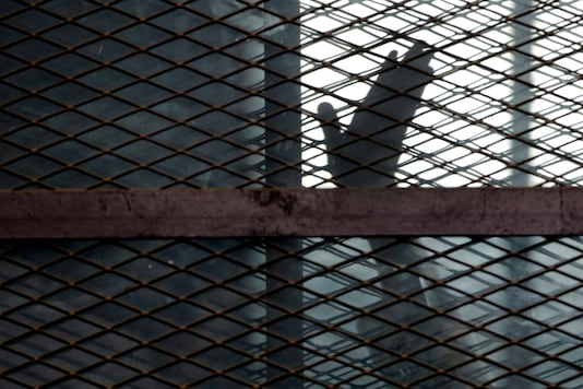 n this Aug. 22, 2015, file photo, a member of the Muslim Brotherhood waves his hand from a defendants cage in a courtroom in Torah prison, southern Cairo, Egypt. (AP Photo/Amr Nabil, File)