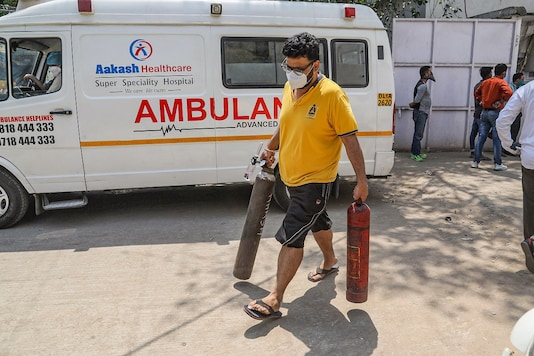A relative of a COVID-19  patient carries empty oxygen cylinders for refilling in New Delhi on Wednesday. (PTI)