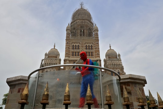 A man dressed as Spiderman sanitizes a railing outside Chhatrapati Shivaji Maharaj Terminus (CSMT) railway station during a lockdown imposed to limit the spread of the coronavirus disease (COVID-19) in Mumbai, India, April 21, 2021. (Reuters Photo)