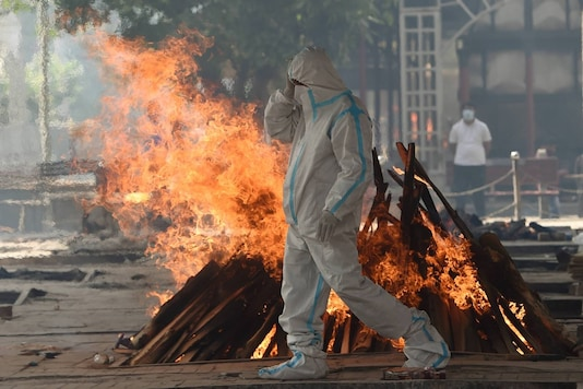 Family member wearing PPE performs last rites of a COVID-19 victim at Nigambodh Ghat crematorium, in New Delhi. (PTI)