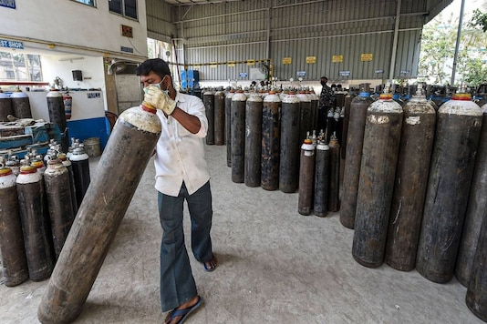 Workers refill cylinders with medical oxygen for supply for COVID-19 patients. (PTI)
