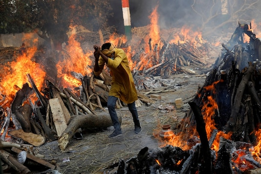A man runs past the burning funeral pyres of those, who died of COVID-19 during a mass cremation, at a crematorium in New Delhi. (Reuters)
