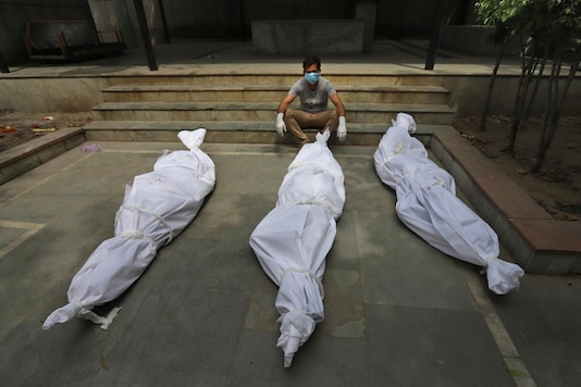 In this April 20, 2021, a man waits for the cremation of a relative who died of COVID-19, placed near bodies of other victims, in New Delhi. (AP)