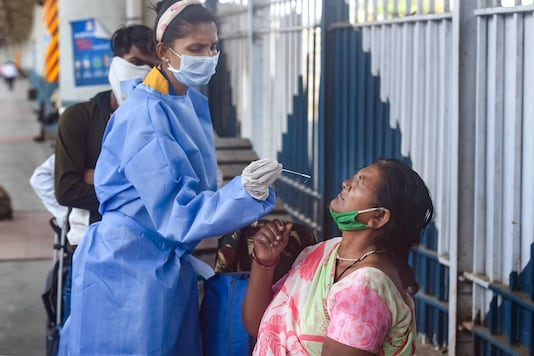 File photo of a health worker collecting swab sample from a passenger at a railway station.