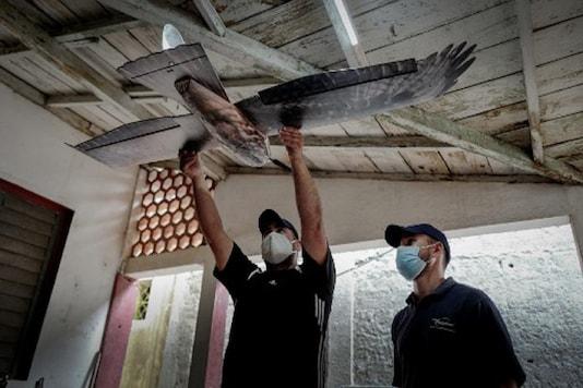 Erick Carmona (L), CEO of Alasoluciones, and member Mykol Diaz (R), work on drones at their workshop in San Nicolas de Bari, Mayabeque province, Cuba.  (Photo by ADALBERTO ROQUE / AFP)