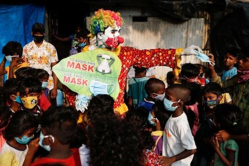 A man distributes face masks to children in a slum. (Reuters)