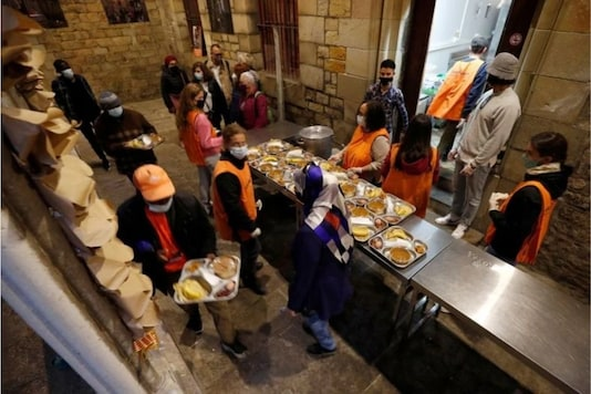 People carry food trays during a charity Ramadan dinner in the cloister at Santa Anna church during the coronavirus disease (COVID-19) outbreak, in Barcelona, Spain, April 28, 2021. REUTERS/Albert Gea