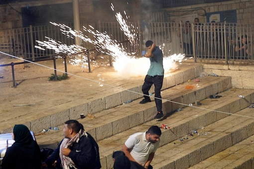 Palestinian youth threw stones, lit fires and tore down police barricades in the streets leading to the walled Old City gates on Saturday night. (AP photo)