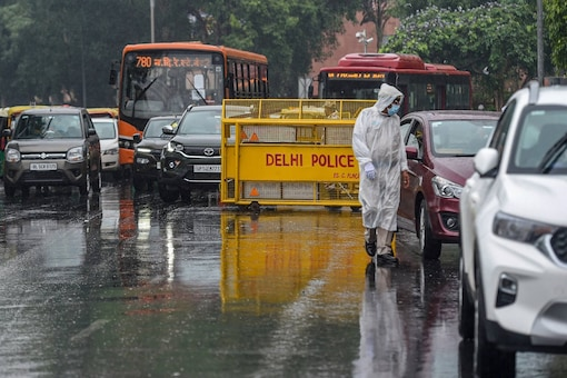A policeman checks vehicles amid a mild shower at Connaught Place, in New Delhi, Wednesday. (PTI)