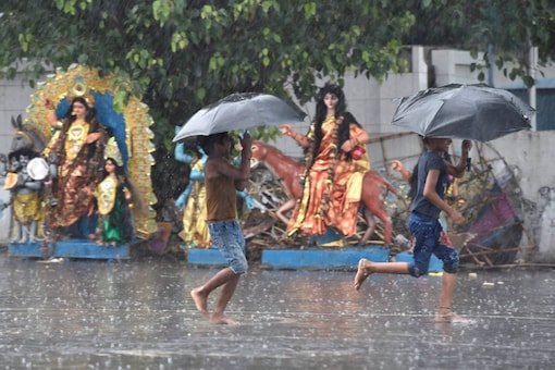 Children covering themselves with umbrellas wade through a watery road in Kolkata