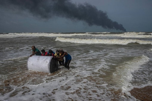 Impoverished Sri Lankans salvage wreck washed off to the shore from burning Singaporean ship MV X-Press Pearl. (PTI)