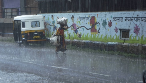 A woman walks with her luggage during heavy rain on a road in Karad, Maharashtra. (PTI Photo)