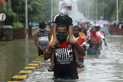 A man carries a child through a waterlogged road after heavy rainfall in Mumbai. Reuters