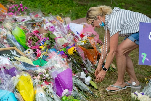 A person leaves flowers at a makeshift memorial at the scene where a Muslim family was killed in what police describe as a hate-motivated attack, at the London Muslim Mosque in London, Ontario, Canada June 12, 2021. REUTERS/Alex Filipe - RC2XYN9HZ1ZM