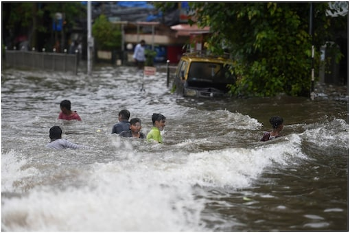 Children play on a waterlogged street after heavy rain, at Sion in Mumbai. (PTI Photo)
