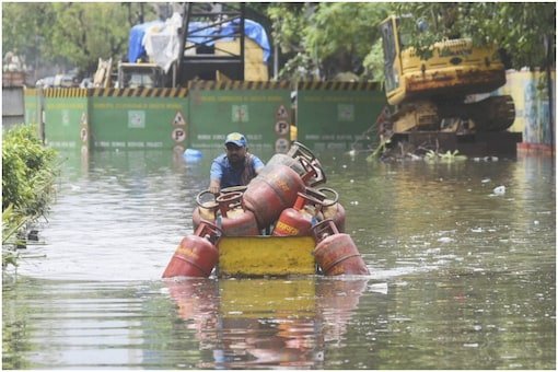 A LPG cylinder supplier wades through waterlogged SV Road after rain, in Mumbai. (PTI Photo)
