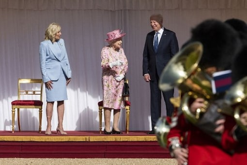 US President Joe Biden (R) and US First Lady Jill Biden (L) speak with Britain's Queen Elizabeth II (C) after watching the military march past at Windsor Castle in Windsor, west of London, on June 13. (Image: AFP)