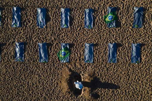 """An activist from the NGO """"Rio de Paz"""" digs a mock grave in the sand by symbolic body bags on Copacabana beach to protest the government's handling of the COVID-19 pandemic in Rio de Janeiro, Brazil"""