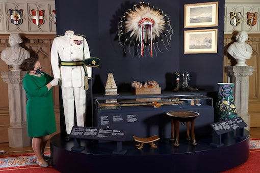 A member of the Royal Collection Trust staff poses for a photograph with items related to Prince Philip's travels at the Prince Philip: A Celebration display in Windsor Castle, Britain, June 24, 2021.  REUTERS/Peter Nicholls