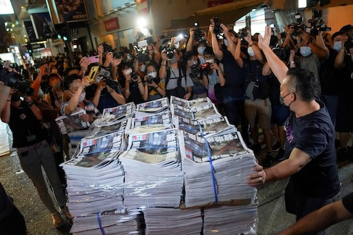 A man gestures as he brings copies of the final edition of Apple Daily, published by Next Digital, to a news stand in Hong Kong, China. (Reuters)