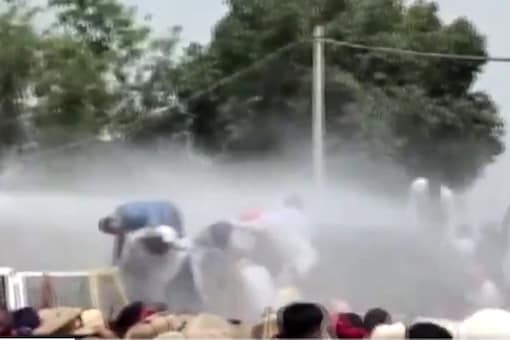 Police use water cannons to disperse Aam Aadmi Party workers.