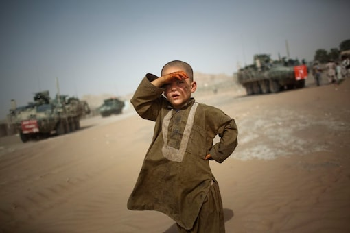 A child looks on as military vehicles cross his village in Spin Boldak, about 100 kilometers southeast of Kandahar, Afghanistan. (AP/File)