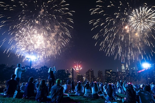 Spectators watch from the Queens borough of New York as fireworks are launched over the East River and the Empire State Building during the Macy's 4th of July Fireworks show, Sunday, July 4, 2021. Credits: AP.