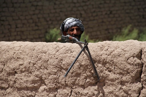 A former Mujahideen keeps watch at a check post as he holds a weapon to support Afghan forces in their fight against Taliban, on the outskirts of Herat province, Afghanistan. (Reuters)