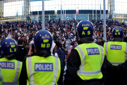A line of police watch supporters outside Wembley Stadium in London (AP)