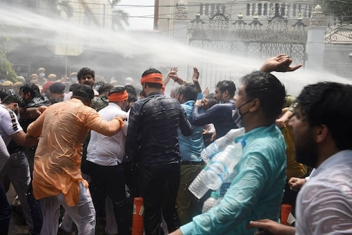 BJP workers and RWA people being hit by police water cannon during a protest over water crisis and an alleged scam, outside Delhi Jal Board Chairman Satyendar Jain's residence in New Delhi, Monday, July 12, 2021. (PTI Photo)