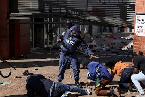 Police officers detain demonstrators as protests continue, following imprisonment of former South Africa President Jacob Zuma, in Katlehong, South Africa. REUTERS