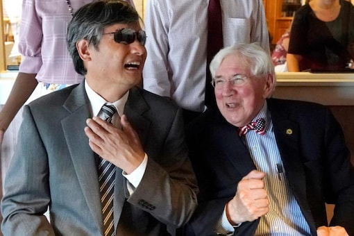 Chen Guangcheng, left, a blind Chinese dissident who escaped to the United States in 2012 and recently became an American citizen, laughs with one of his attorneys, George Bruno, Thursday, July 8, 2021, during a lunch to celebrate his citizenship in Manchester, N.H. (AP Photo/Elise Amendola)