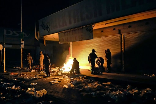 South African Defence Force soldiers keep themselves warm around a fire while stationed in Alexandra Township, near Johannesburg, to assist police in quelling looting and rioting. (AP)