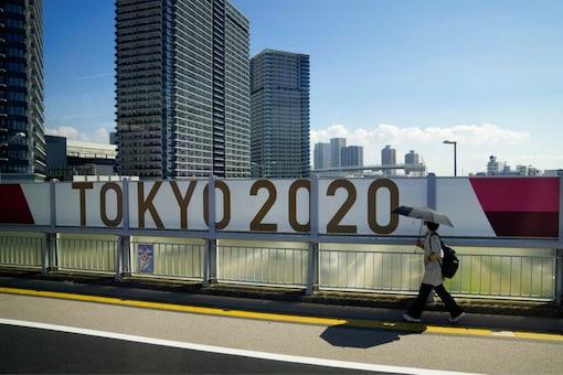 A woman walks on a bridge past a Tokyo 2020 banner ahead of the 2020 Summer Olympics (AP)