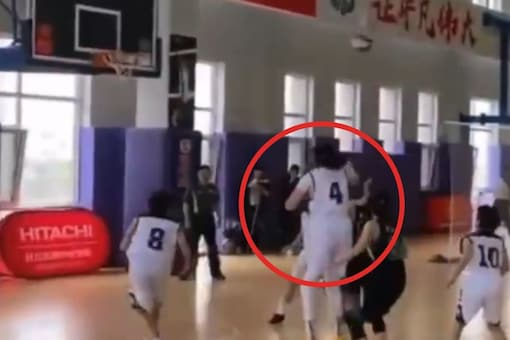 Video grab of 14-year-old girl with a height of 7ft playing basketball.  (Credit: Twitter)