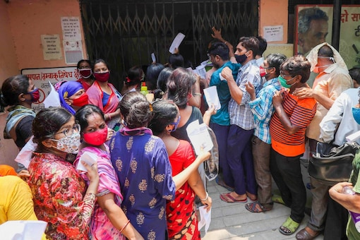 Jaipur: People, flout social distancing norms as they wait to receive a dose of COVID-19 vaccine at a government dispensary in Jaipur, Saturday, July 17, 2021.