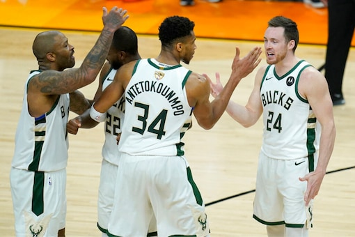 Milwaukee Bucks' P.J. Tucker, from left, celebrates with Khris Middleton, Giannis Antetokounmpo and Pat Connaughton during the second half of Game 5 of basketball's NBA Finals against the Phoenix Suns (AP)