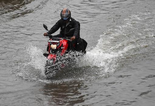 A commuter wades through a waterlogged street as heavy rain continues at Santacruz- Chembur Link Road, in Mumbai. (PTI)
