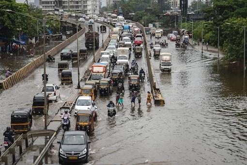 Mumbai: A commuter wades through a waterlogged street as heavy rain continues at Santacruz- Chembur Link Road, in Mumbai. (PTI)