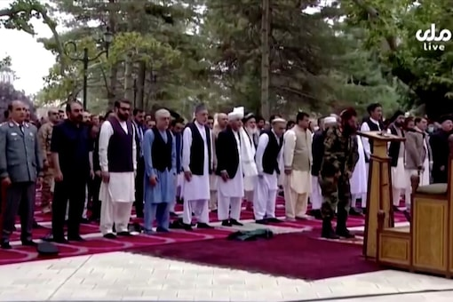 Afghanistan's President Ashraf Ghani (front row) attends Eid al-Adha prayers at the presidential palace, moments before the sounds of rocket explosions can be heard, in Kabul, Afghanistan on Tuesday in this still image taken from TV footage.